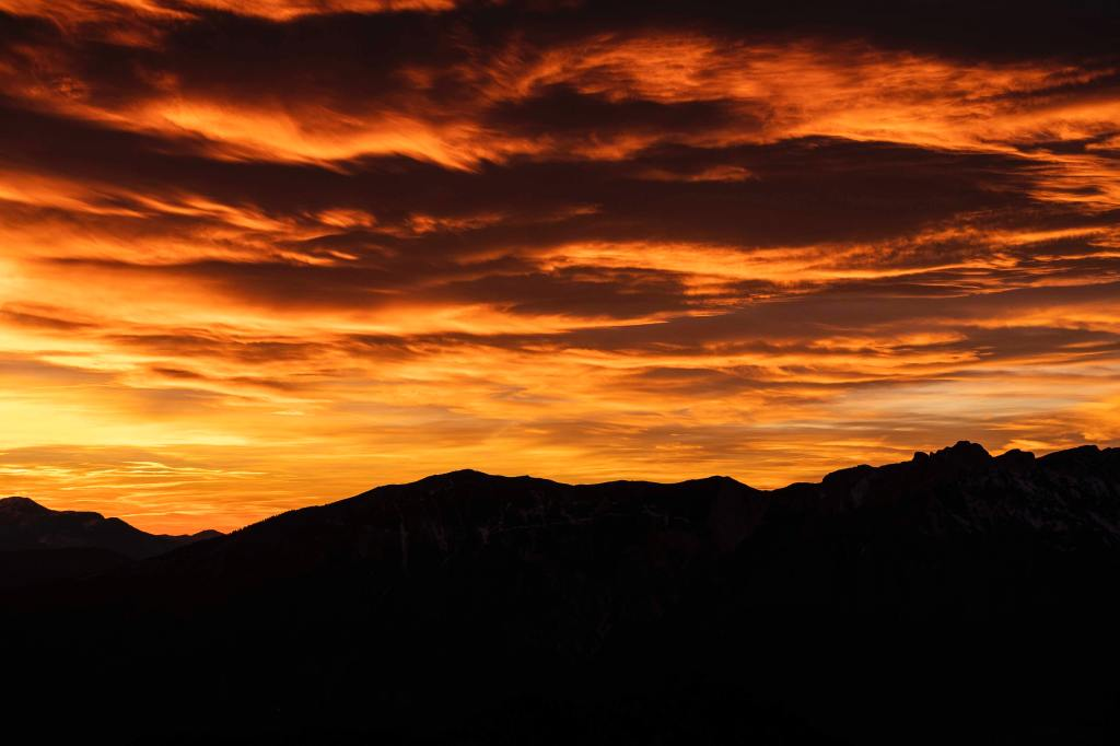 A photo of a dark mountainside highlighted by the vibrant sky as the sun sets behind it